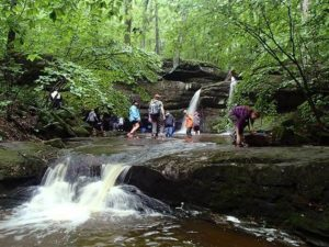 People Hiking Near Waterfall